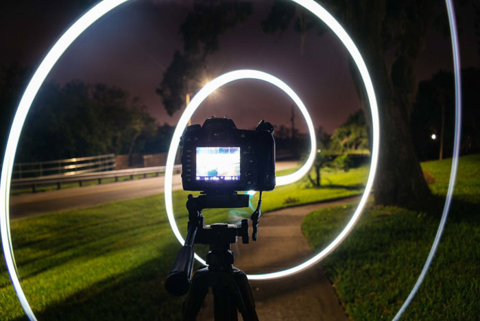 A DSLR camera on a tripod surrounded by a white light spiral