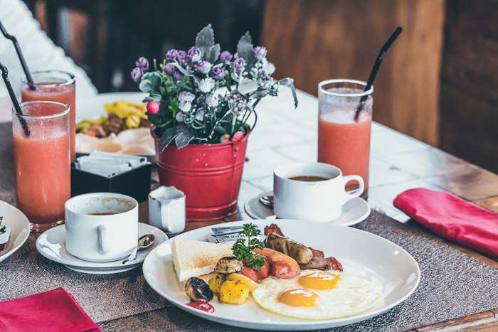 Pretty food photography of a lunch setup with plate of food, coffee cups and glasses of juice, shot with a macro lens for still life photography
