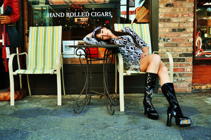 A female poses on a seat outside a shop for fashion model photography