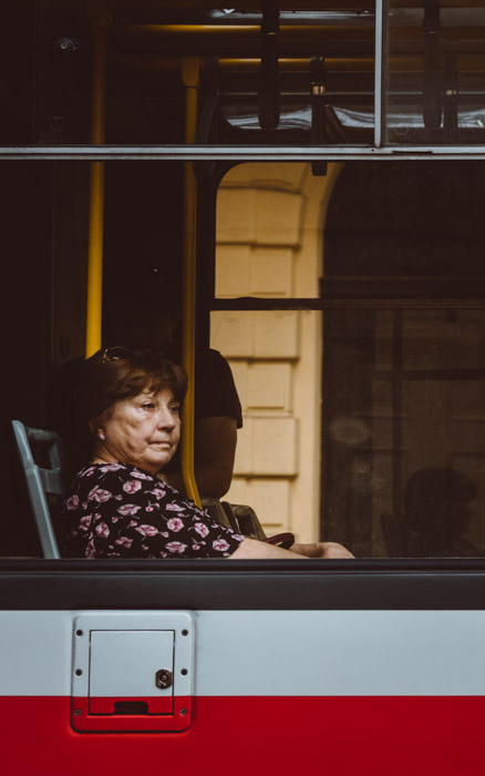 A woman sitting at the window of a bus