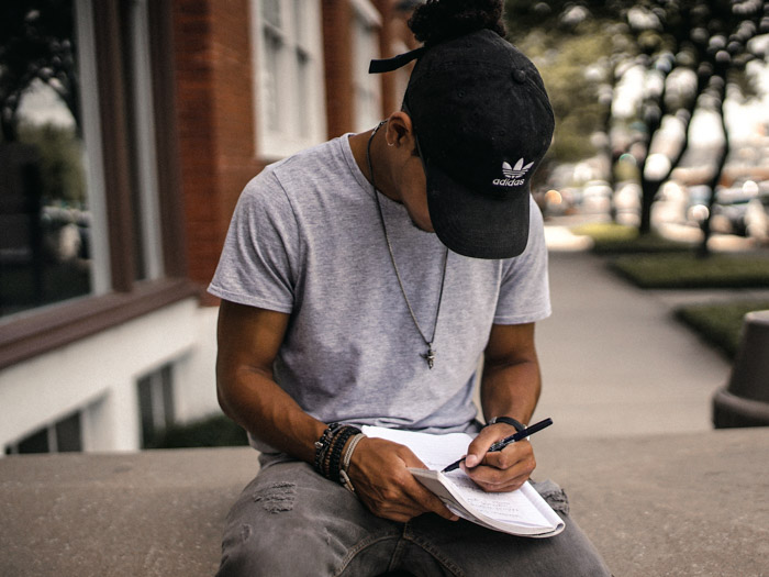 A man in black hat sitting on a stone wall writing a model release form for photography