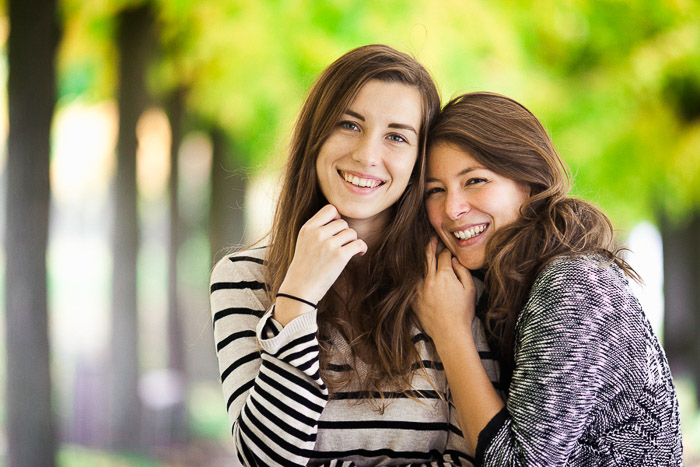 An outdoor portrait of two female friends hugging casually in Brühl, Germany