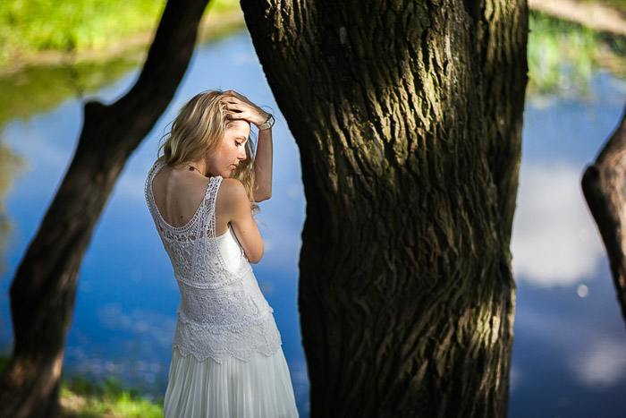 An outdoor portrait photography shot of a girl posing by a tree and water in park in Saint Petersburg
