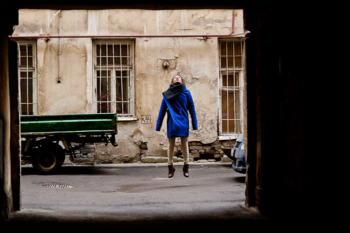 A natural light photography portrait of a girl jumping in the yards of Saint Petersburg