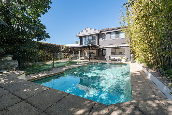 A real estate photography exterior shot of a swimming pool in the foreground of a large house