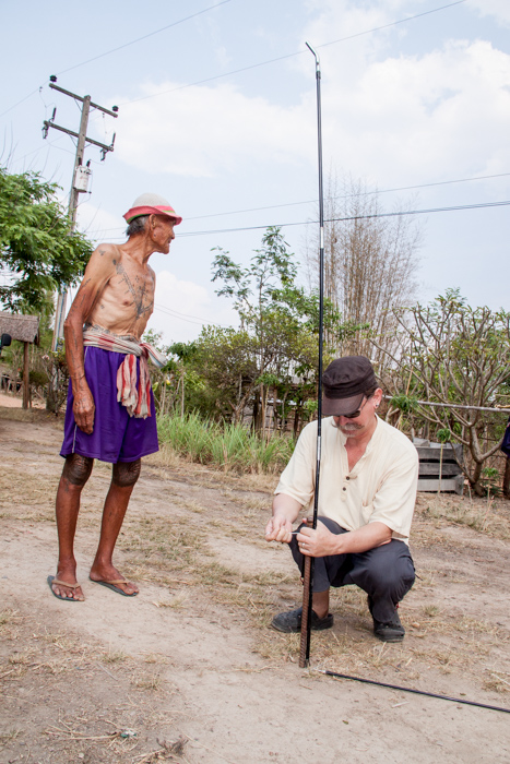 A Karen man watches the photographer setting up a outdoor portrait photography studio in Om Koi district, northern Thailand.