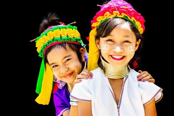 Photo of two Kayan girls enjoying having their portrait made in an outdoor portrait photography studio in their village in north Thailand.