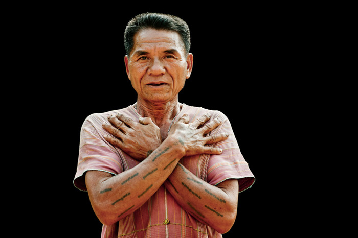 A Karen man shows off his traditional tattoos against a black ground in an outdoor portrait photography studio.