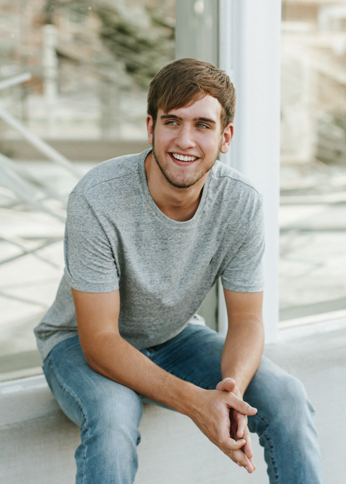 An outdoor portrait photography shot of a young man posing casually