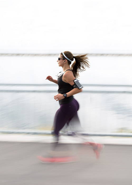 A panned shot of a female jogger