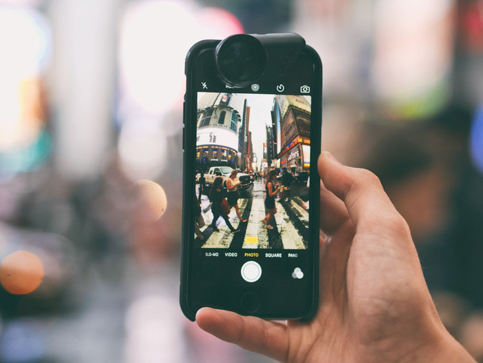 A hand holding a smartphone to take a photo of a busy street scene