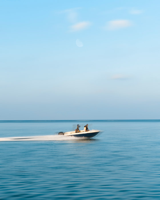 A panned shot of a speedboat on the blue ocean