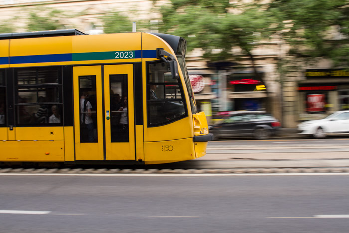 A shot of a yellow tram moving on the street