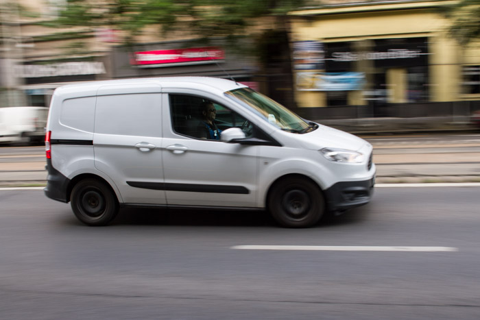A blurry shot of a white van driving on the street