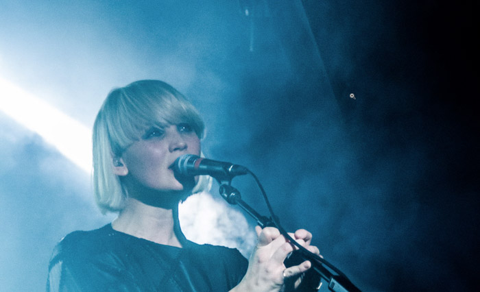 A grainy concert photography shot of a female singer - example of an image that needs photo retouching