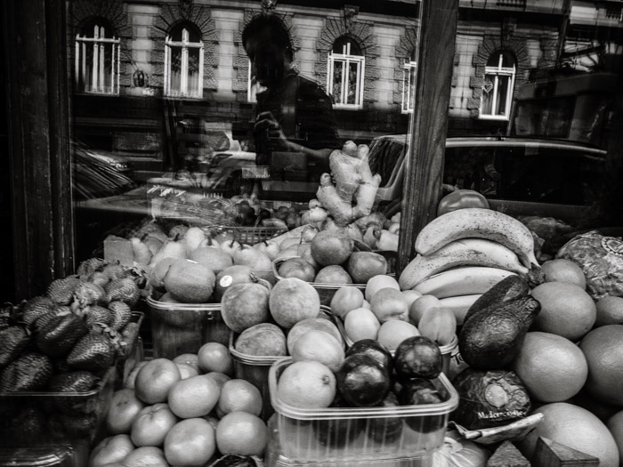 Black and white street photo of a man reflected in the window of a fruit and vegetable shop