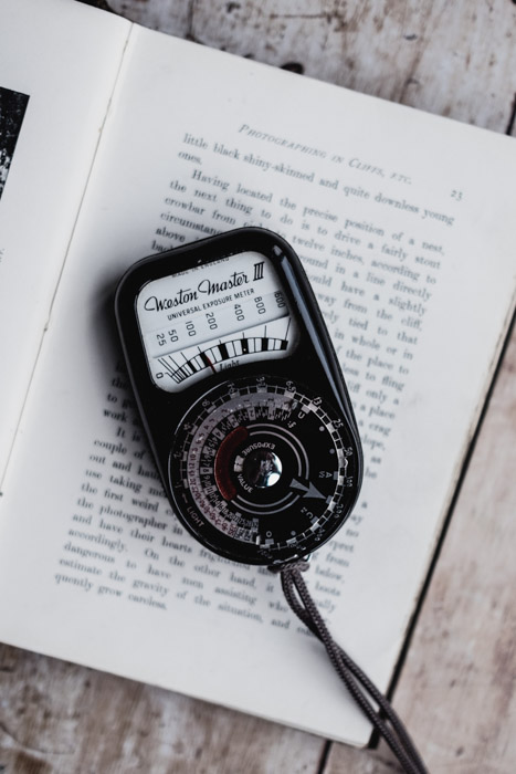 A photography light meter resting on a book