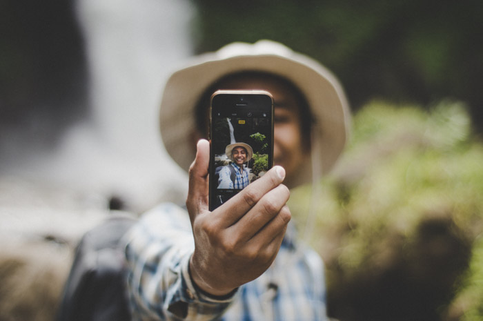 A man holding a smartphone and taking a selfie