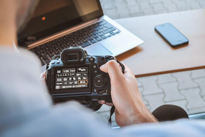 Close up of a man looking through a digital camera