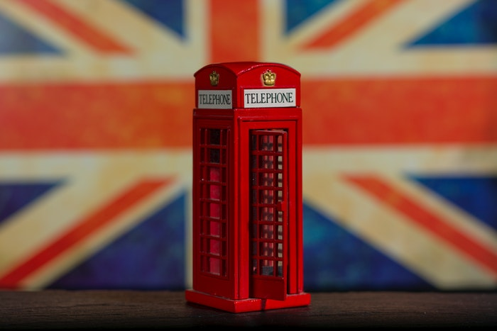 Red toy phone booth with british flag background