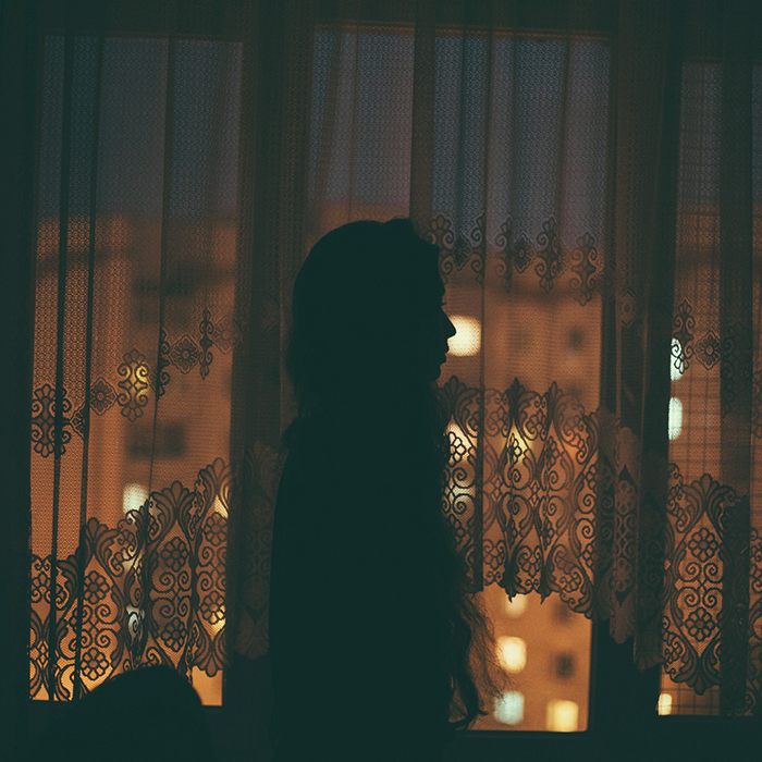 Atmospheric indoor photography silhouette of a girl standing by a window
