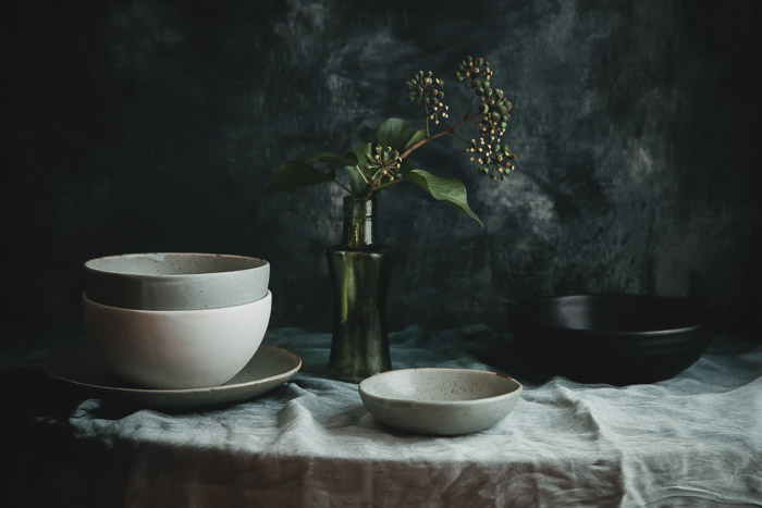 Still life photography of pottery bowls and a flower in a vase on a table, with dark background.