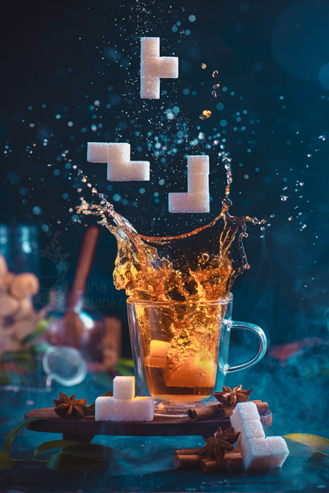 Splash of tea in a double wall glass with sugar Tetris pieces. 8-bit video game in real life concept with copy space. Creative action food photography. Still life photography ideas