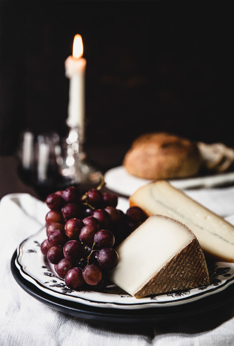 Still life photography of cheese and grapes on a plate.