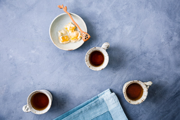 Still life photography shot of three teacups with honeycomb, overhead shot on blue background.