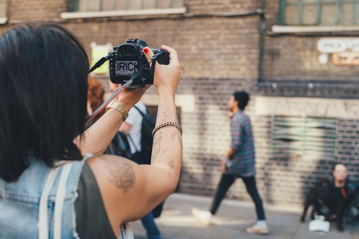 Una fotógrafa callejera sosteniendo una cámara réflex digital y tomando fotografías francas de los transeúntes