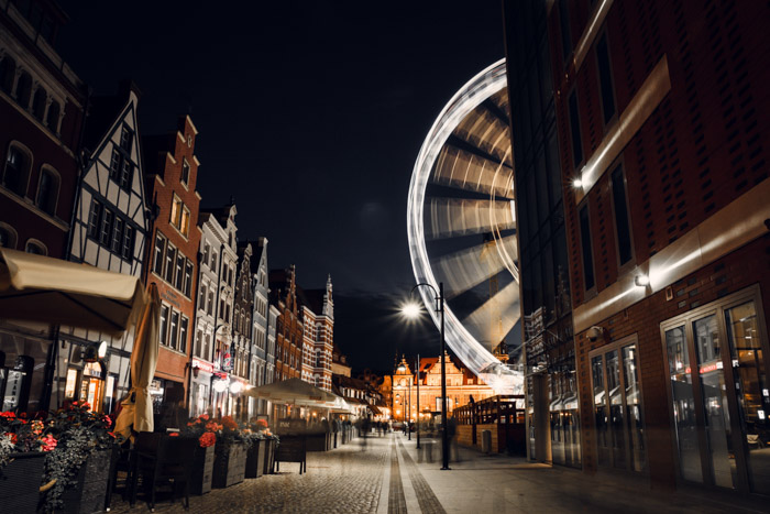 A street scene at night with a moving ferris wheel captured with a time-lapse camera