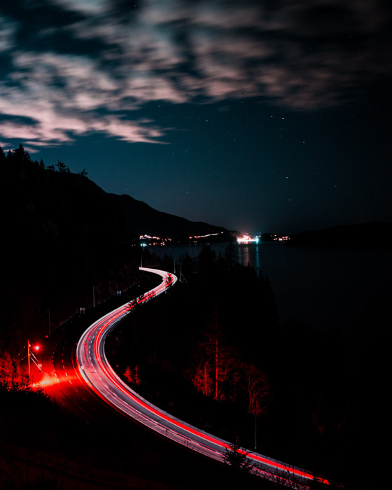 Stunning time lapse photography of pink light trails streaming through a road at night
