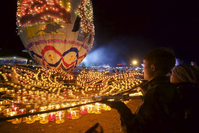 Night photography of people watching a light display - travel photography checklist.