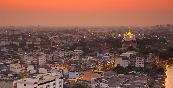 Cityscape view of Bangkok skyline with Golden Mount in the distance at sunset.