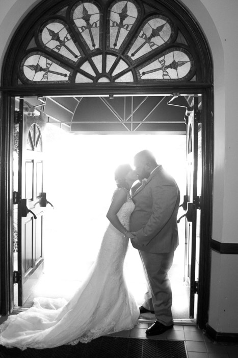 A black and white photo of the newlywed couple kissing under an arched doorway - wedding photography lighting tips