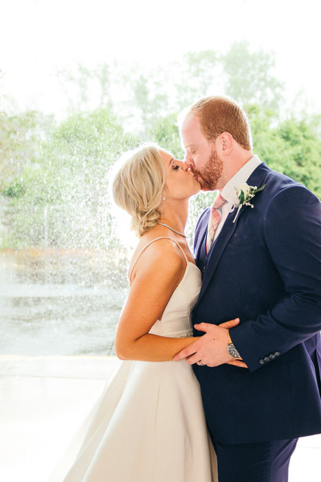 A photo of the newlywed couplekissing outdoors - wedding photography lights