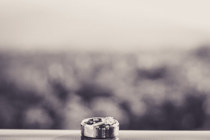 A black and white close up photo oof a wedding ring on a window sill.