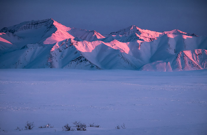 hills covered in snow at sunset with pinkish glow on them