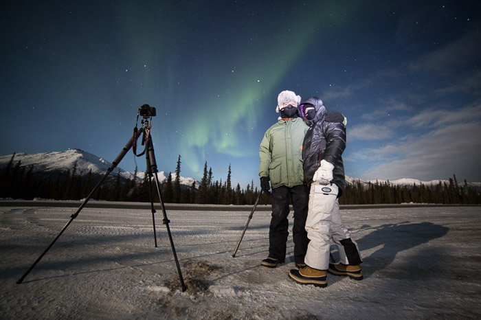 Photo of two photographers with camera and tripod shooting the northern lights. Winter photography.