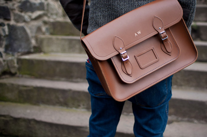 close up picture of a man carrying a brown leather camera bag