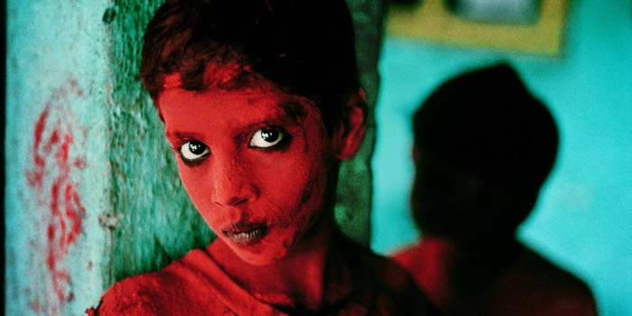 Steve McCurry portrait of a child painted with red face paint against a green wall - famous photographers work