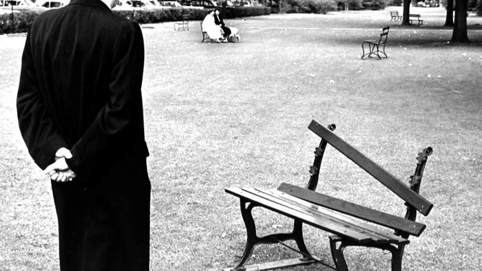 Andre Kertesz photo of a man standing in front of at a broken park bench