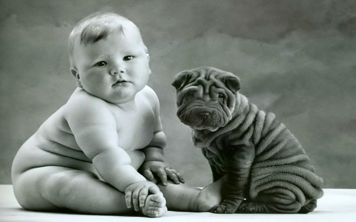Anne Geddes black and white portrait of a chubby baby posed beside a puppy