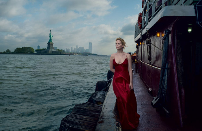 Annie Leibovitz portrait of a girl in a red evening dress standing on a dock with sea and empire state building behind her