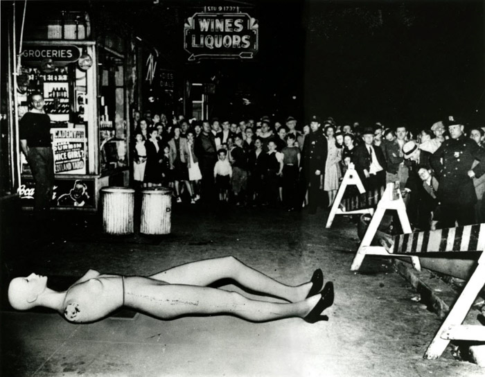 Weegee photo of a crowd of people looking at a crime scene, with a shop mannequin placed on the ground