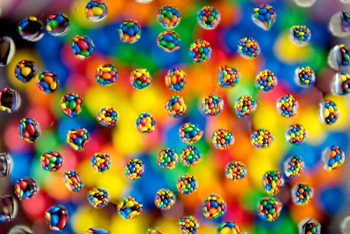 A fun water droplet photography shot of circles of brightly colored sweets with droplets on a bokeh background
