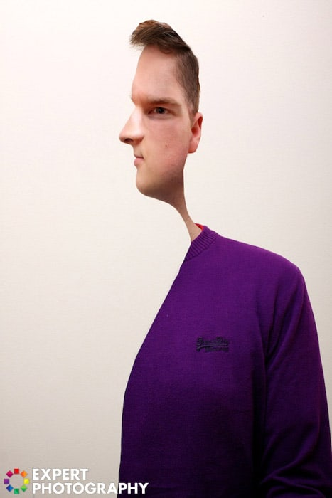 A man in purple jumper, with a creative cut out effect on his face which makes him look like a subject in a Picasso painting