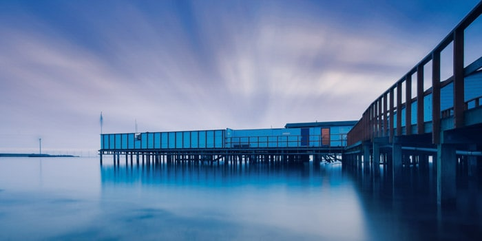 A daytime long exposure shot of a pier