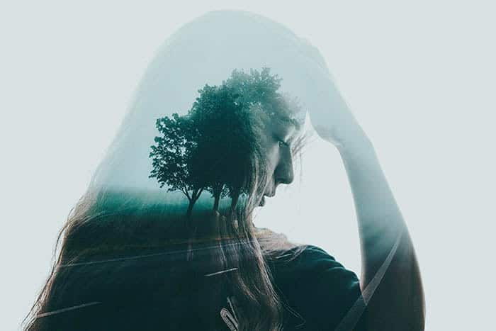 Beautiful and atmospheric double exposure of a girl with her hand to your head, layered with a photo of trees lining a roadway