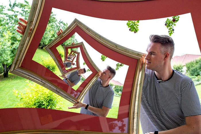 Photoshop ideas example of a droste effect shot of a man holding a photo frame, with the same image repeated within the frame and within that frame